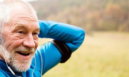Sundhed. .Ældre løber strækker ud under løbetur.